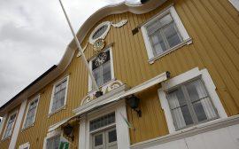 Bild på rådhuset i Ulricehamn. En gul träbyggnad med vita fönster.