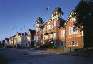 Bild på Folkets hus i Ulricehamn i solsken. Huset är mörkrosa med vita fönster och har två torn och en tjusig trappa.
