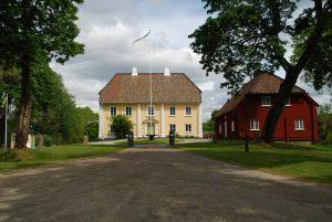 Bild på Källebacka. En ljusgul herrgårdsbyggnad. Bredvid en röd flygelbyggnad i trä. en lång grusväg leder fram till husen.