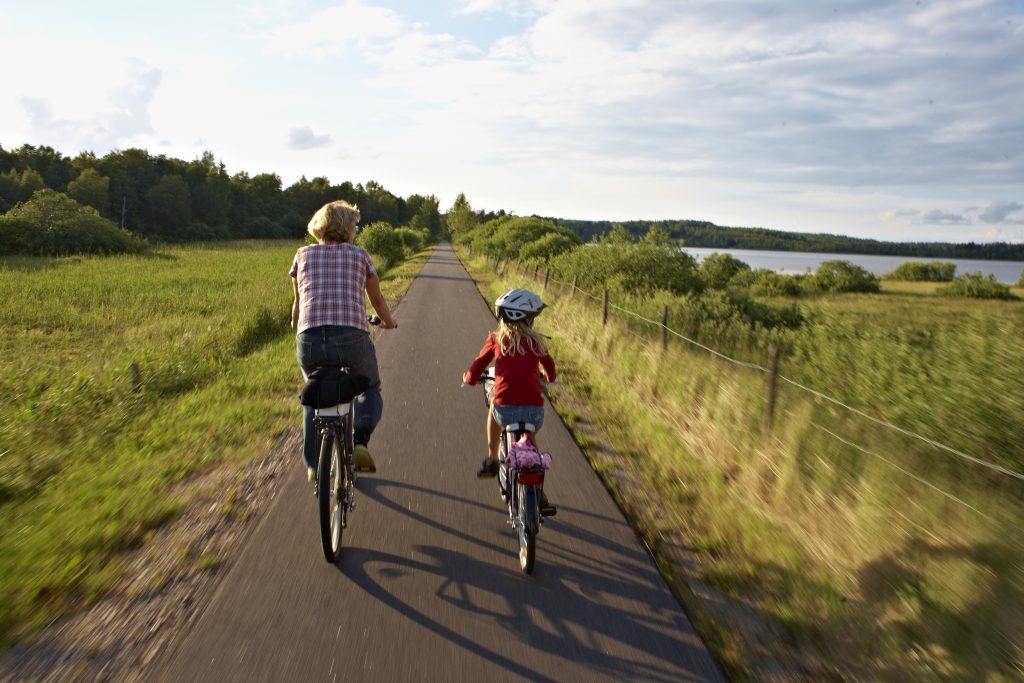 Bild på en vuxen och ett barn som cyklar på en cykelväg.