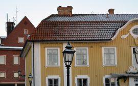 Bild på Ulricehamns rådhus, en gul träbyggnad som är stadens äldsta byggnad. I bakgrunden stadshuset i rött tegel.