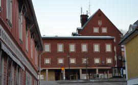 Bild på stadshuset taget från Bogesundsgatan. Huset är en röd tegelbyggnad i vinkel och i flera våningar.