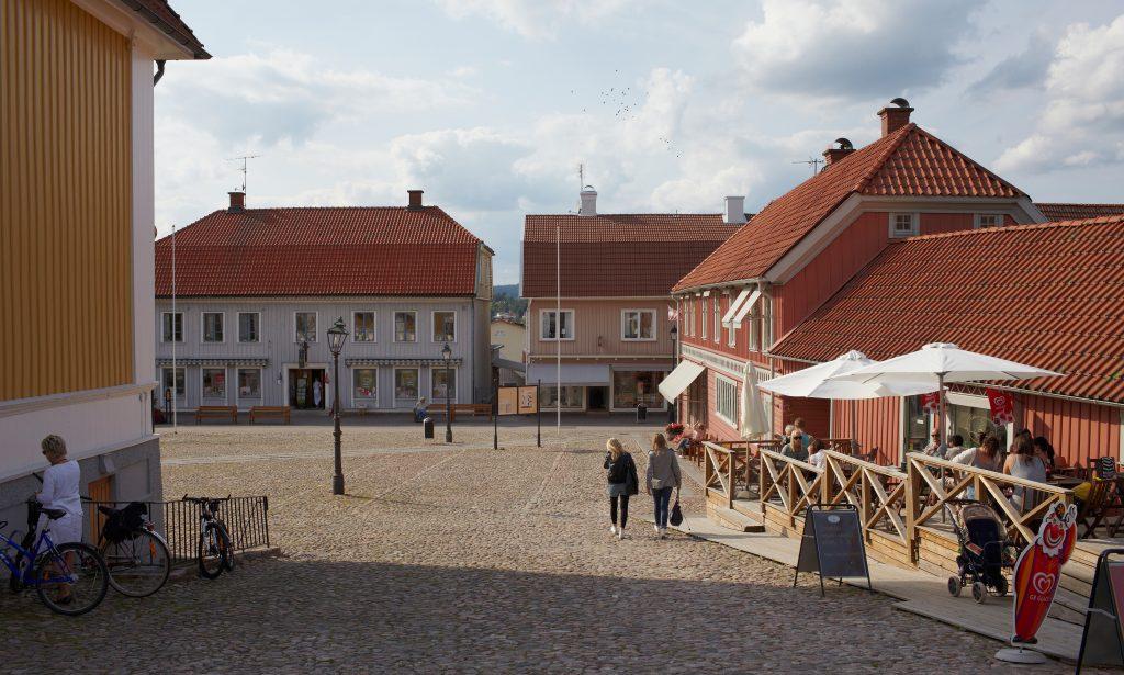 Bild på stora torget i Ulricehamn med kullerstenar och trähus runt omkring.
