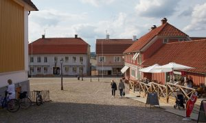 iIld på stora torget i Ulricehamn med gammal bevarad träbyggnad samt kullersten på marken.