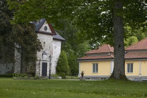 Bild på Vinsarp. En grå stenbyggnad och bredvid en ljusgul byggnad i puts med rött tegeltak.