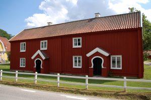 Bild på Bäckagården i Marbäck, en röd träbyggnad i två våningar med vita fönster.