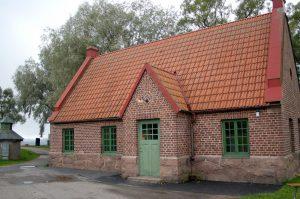 Bild på Gamla vattenverket i Ulricehamn. En låg röd tegelbyggnad me grön dörr och gröna fönster.