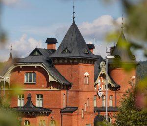 Bild på Stationshuset i Ulricehamn. En tegelbyggnad med två torn och svart tak.