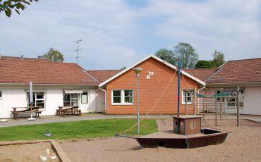 Bild på Pastellens förskola och skolgården med sandlåda med en båt i förgrunden