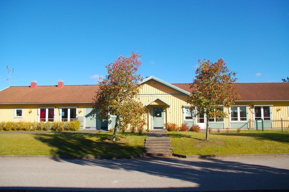 Bild på Hästhovens förskola som är ett envåningshus i gult trä och rött tak.