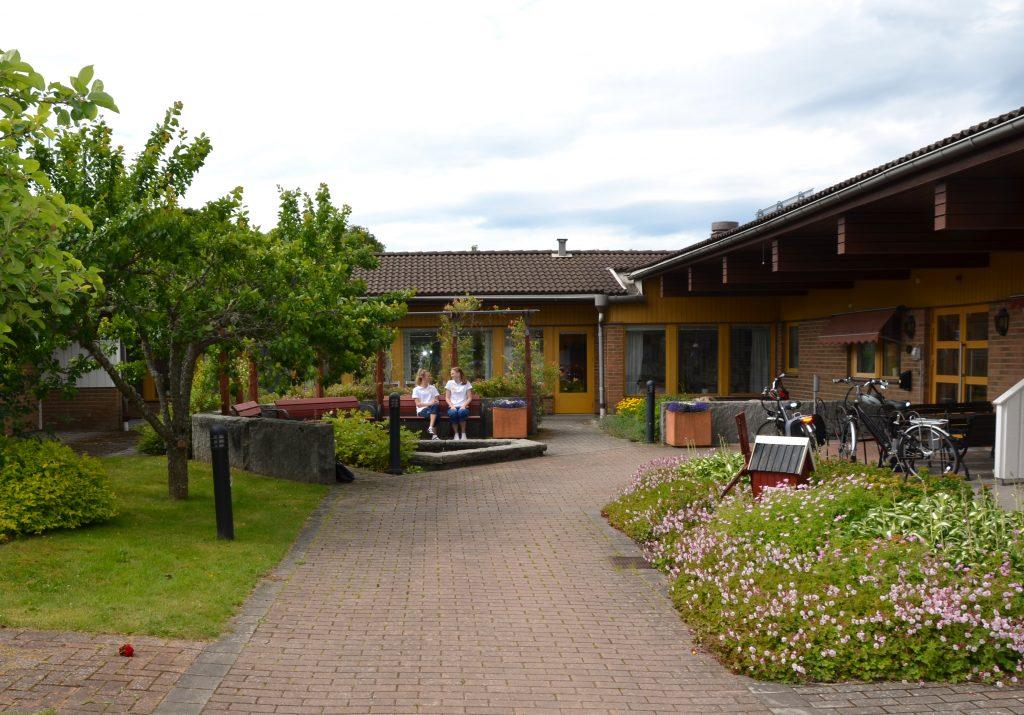Bild på Hökerumsgården och delar av den gröna innergården framför entrén.