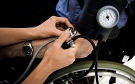 En person tar blodtrycket på en person i rullstol
