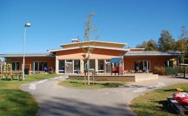 Bild på Stadsskogens förskola en solig dag. Gården i förgrunden och förskolan i bakgrunden.