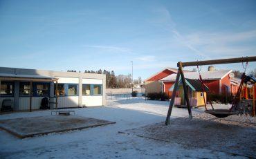 Bild på Träskons förskola med ett snötäcke på lekplatsen. Huset är en låg mindre byggnad med platt tak.