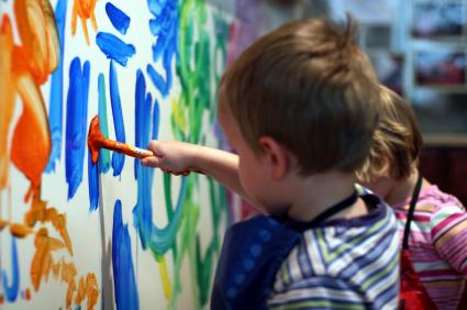 Bild på en tre-åring som målar på en vägg med blått och orange