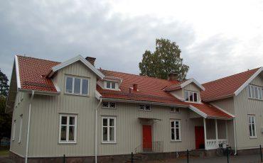 Bild på Nyckelpigans förskola som är beige träbyggnad med vackert rött tegeltak och röda dörrar.