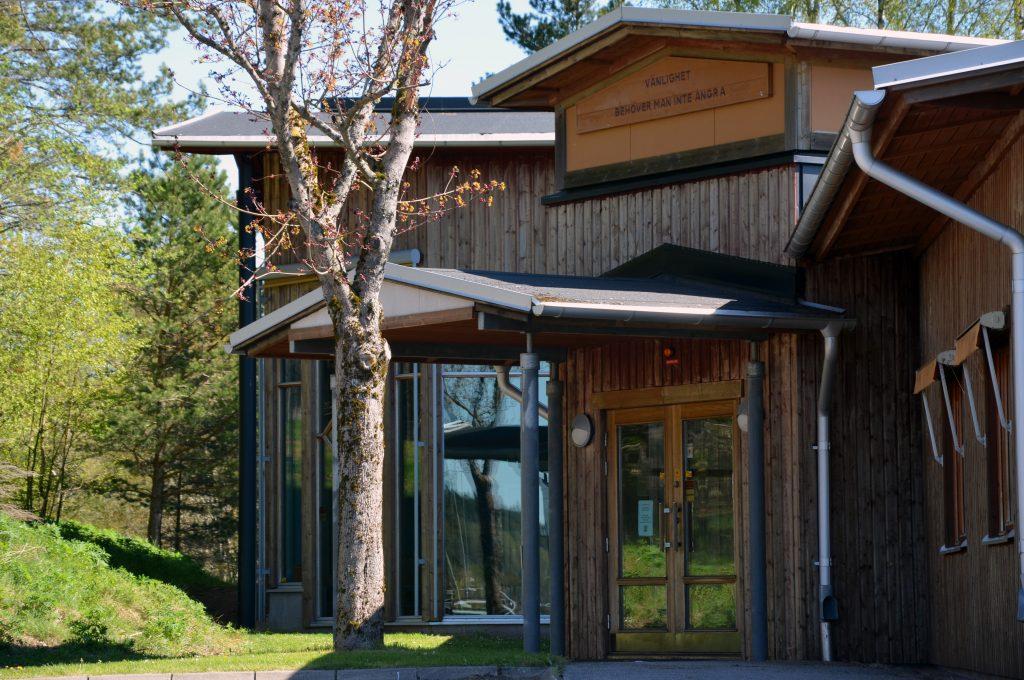 En bild på entrén vid Blidsbergs skola. Hus är i trä med större glaspartier