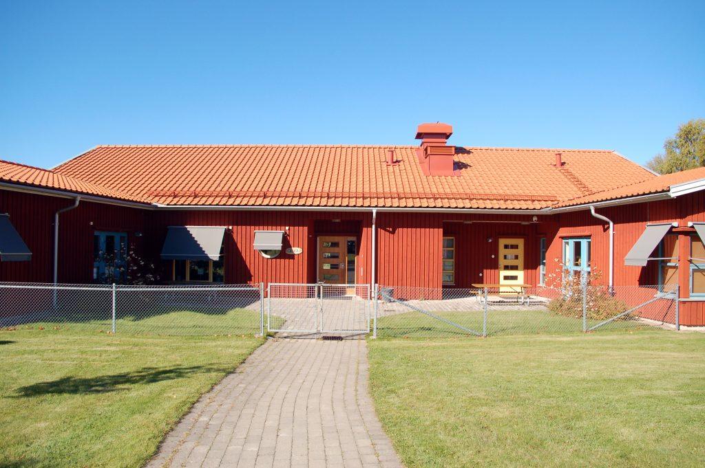 Bild på Marbäcks förskola som är en enplanshus i rött trä byggt i vinkel..
