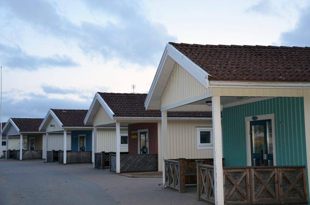 Bild på Ulrikaskolans ingångar på baksidan av husen som är i ljusgult trä.