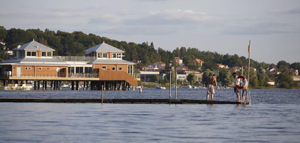 Kallbadhuset i Ulricehamn med människor i förgrunden som badar från en brygga. Foto: Jan Töve