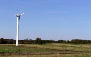 Bild på ett vindkraftverk på en slätt med grönt gräs och klarblå himmel.