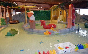 Bild på plaskbassäng med badlekasker och större figurer man kan sitta på i bassängen.