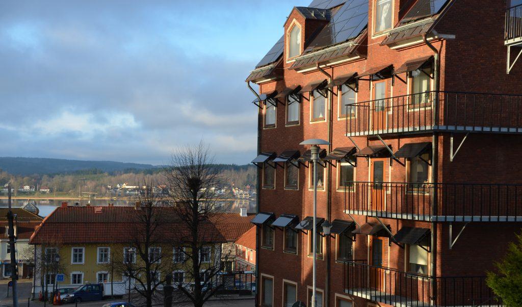 Bild på stadshuset i Ulricehamn, en röd tegelbyggnad i flera våningar med staden i bakgrunden