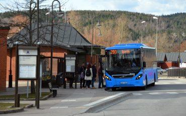 Blå buss framför en busshållplats
