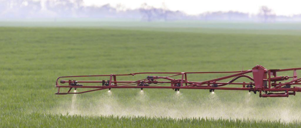 Bild på en jordbruksmaskin som sprider växtskyddsmedel på en åker