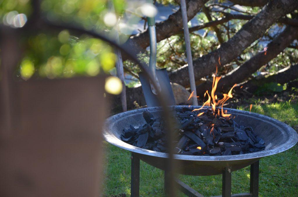 Bild på en grill i en trädgård där en eld har tänts