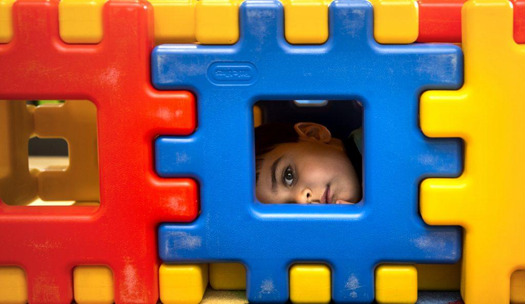 Bild på ett barn som kikar fram ur ett fönster i en färgglad vägg