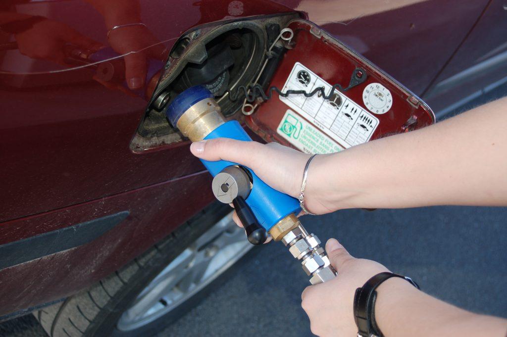 Bild på händer som håller i ett munstycke för tankning av fordonsgas.