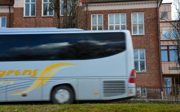 Bild på en buss som kör förbi utanför Stenbocksskolan