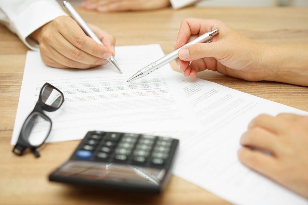 Miniräknare och personers händer som skriver på papper