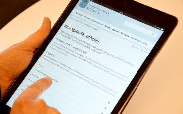 Bild på en person som pekar på en ipad som visar den digitala anslagstavlan.