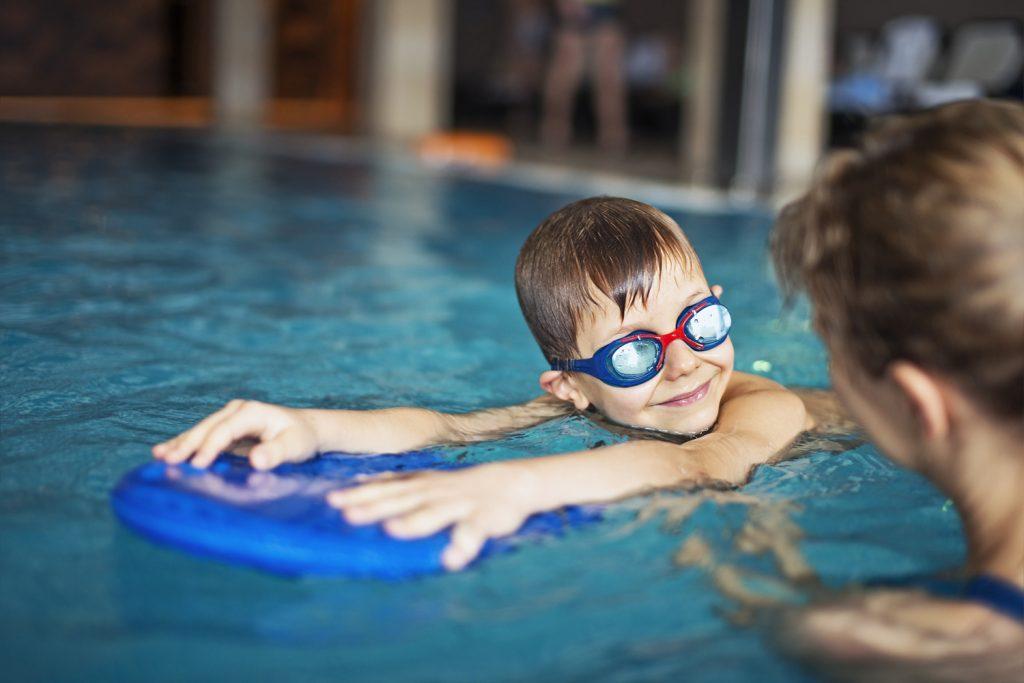Bild på barn som simmar med en flytdyna och har simglasögon.