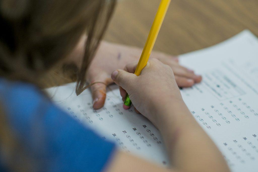 Bild på barn som fyller i ett prov med en blyertspenna