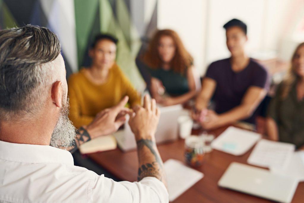 Kollegor som sitter och lyssnar runt ett bord. En person har tatueringar på sin arm.