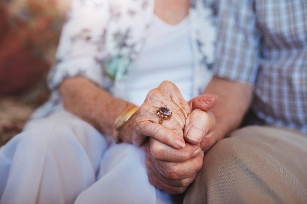 Bild på äldre personer som håller varandra i handen