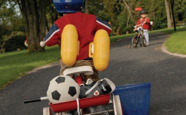 Bild på barn på trehjuling med fotboll på flaket och simpuffar på ryggen.