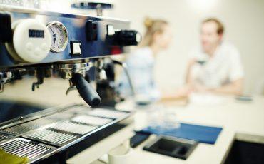 Kaffemaskin med personer i bakgrunden