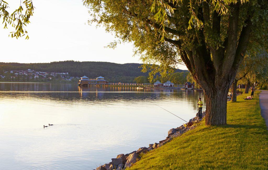 Bild på strandpromenaden vid sjön Åsunden som ligger spegelblank.