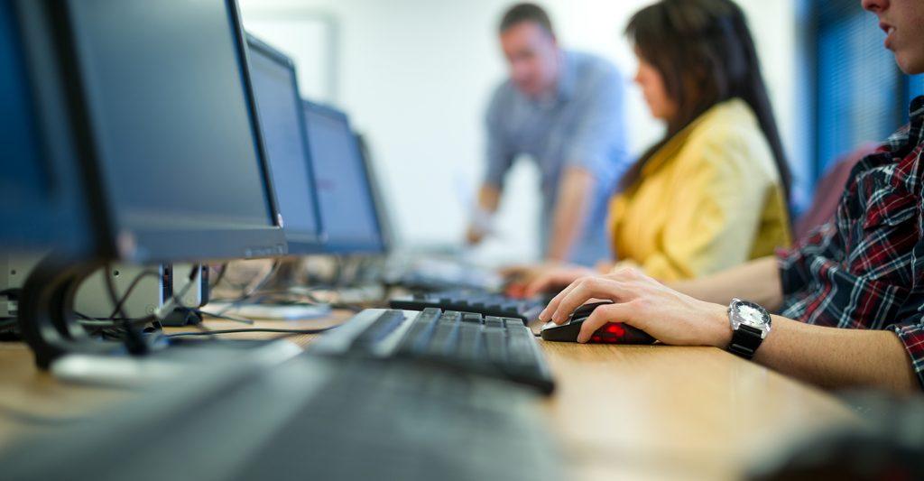 Bild på personer som sitter i en datasal framför datorskärmar