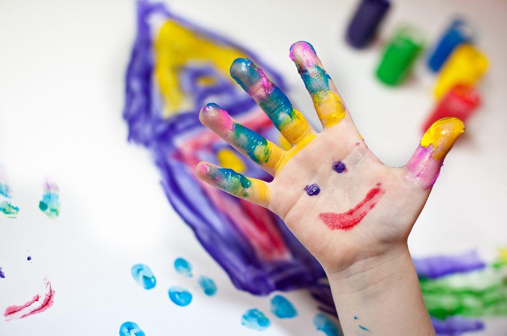 Barnhand som målar med fingerfärg