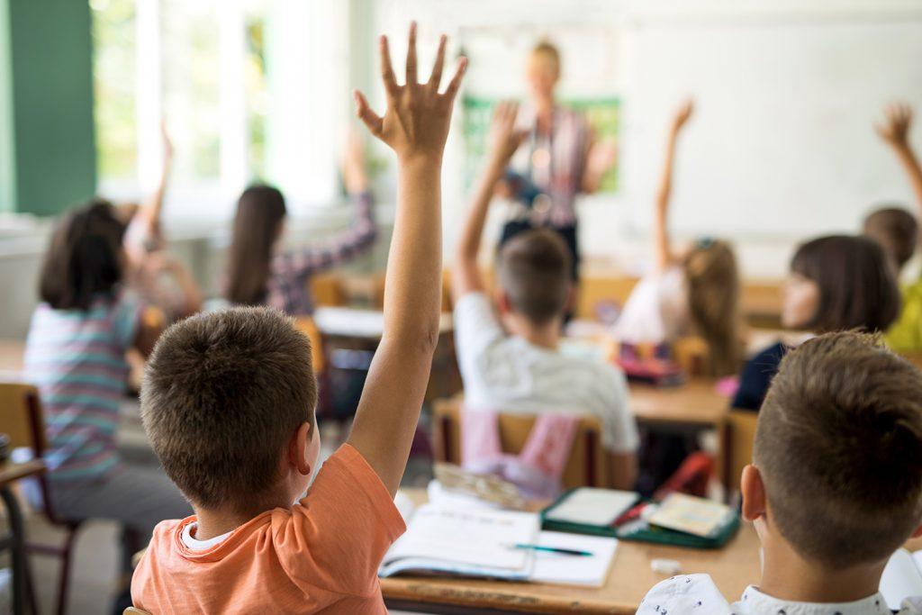 Bild på barn som räcker upp handen i ett klassrum