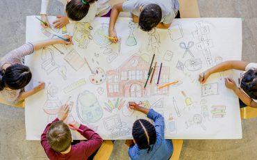 Bild på barn som ritar en skola på ett papper lika stort som ett bord.