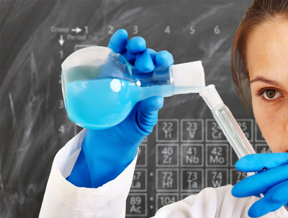 Bild på elev med blå handskar som häller blå vätska i en behållare