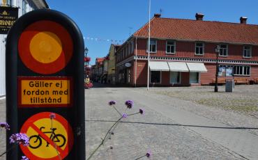 Biild på en vägskylt med förbud för cykeltrafik och motorfordon. i bakgrunden stora torget och gågatan i Ulricehamn.