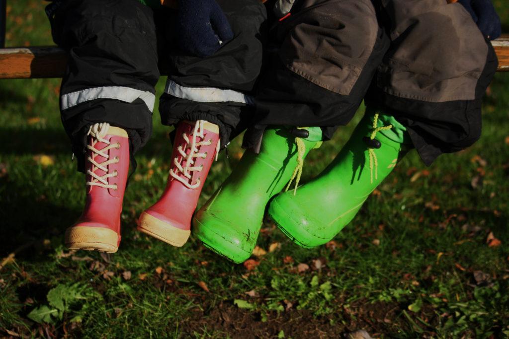 Barnfötter med gummistövlar