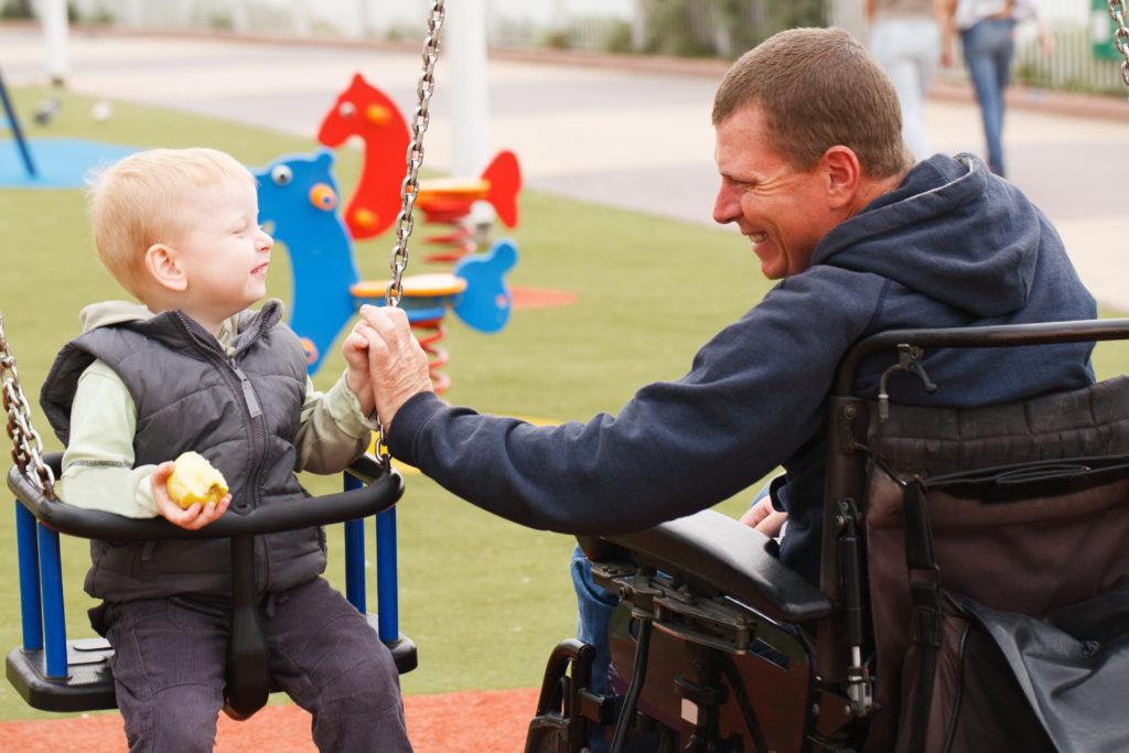 Barn i en gunga och en man i en rullstol som håller i barnet.